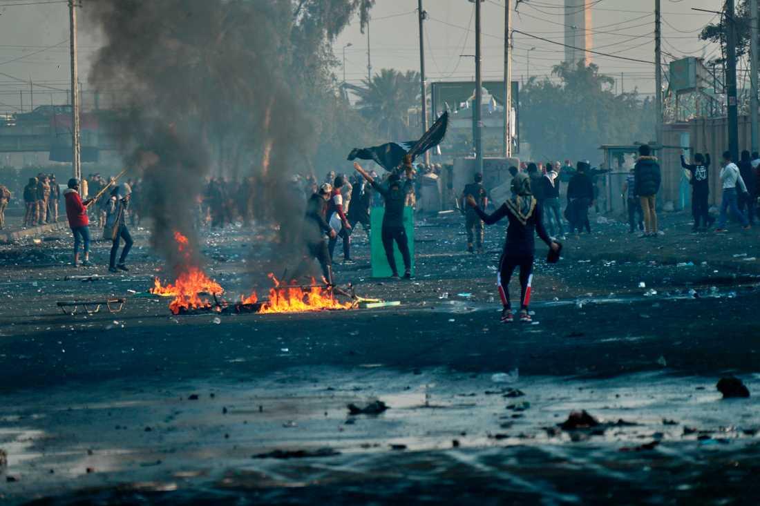 Regeringsfientliga demonstranter under drabbningar med säkerhetsstyrkor i Iraks huvudstad Bagdad på måndagen.