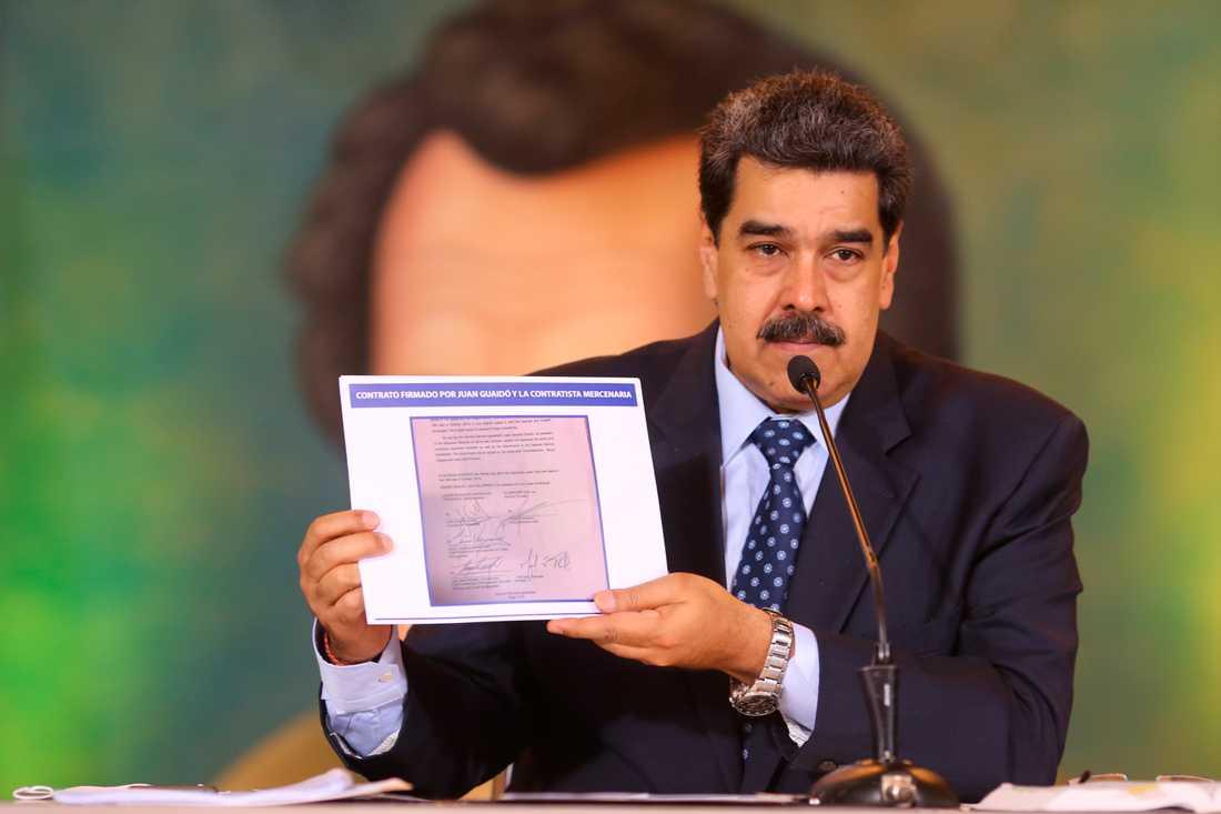 Venezuelas president Nicolás Maduro visar upp en kopia av ett avtal med säkerhetsföretaget Silvercorp med vad han påstår är oppositionsledaren Juan Guaidós underskrift.