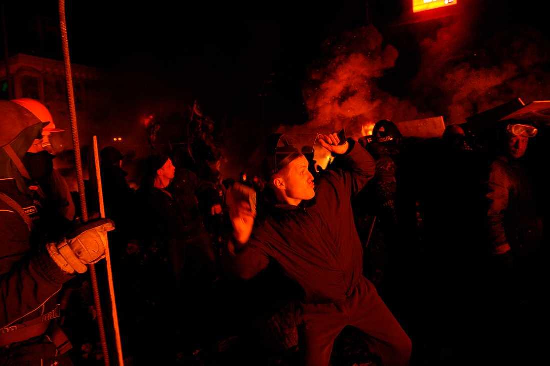 En man skriker ursinnigt ut med Janukovytj och kastar en sten.