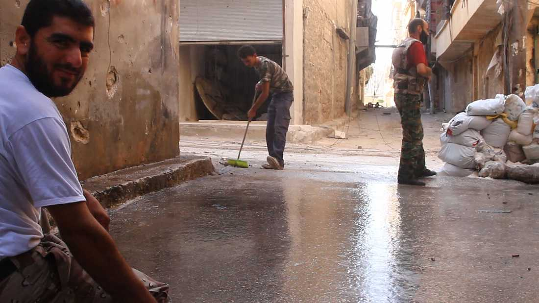 Rebellerna städar i gränden i Aleppo där de byggt en postering.
