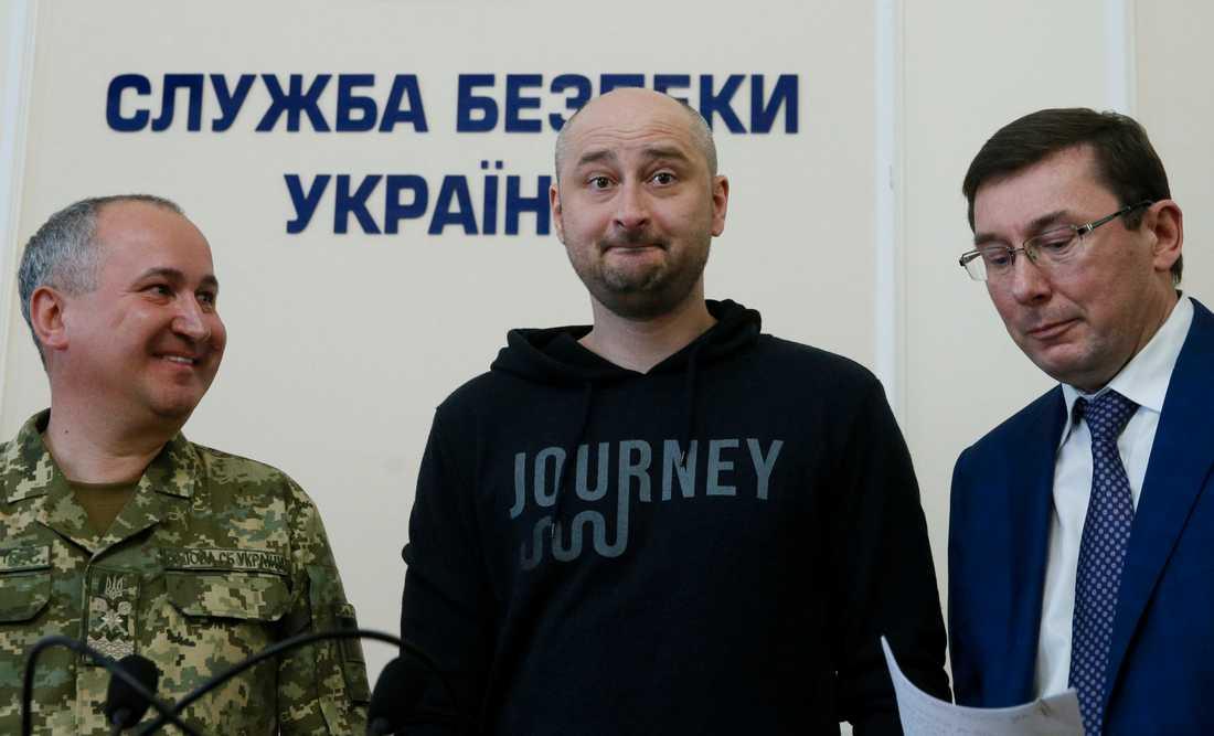 Den ryske journalisten Arkadij Babtjenko (i mitten ) som i tisdags rapporterades mördad – har dykt upp vid liv på en presskonferens i den ukrainska huvudstaden Kiev. Här står han mellan den ryske chefsåklagaren (till höger) och chefen för den ukrainska säkerhetstjänsten (till vänster).