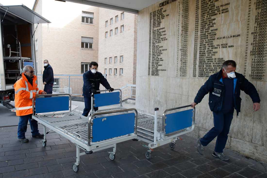 Sjukhuspersonal med nya sjukhussängar utanför sjukhuset i Codogno i norra Italien i förra veckan. Arkivbild.