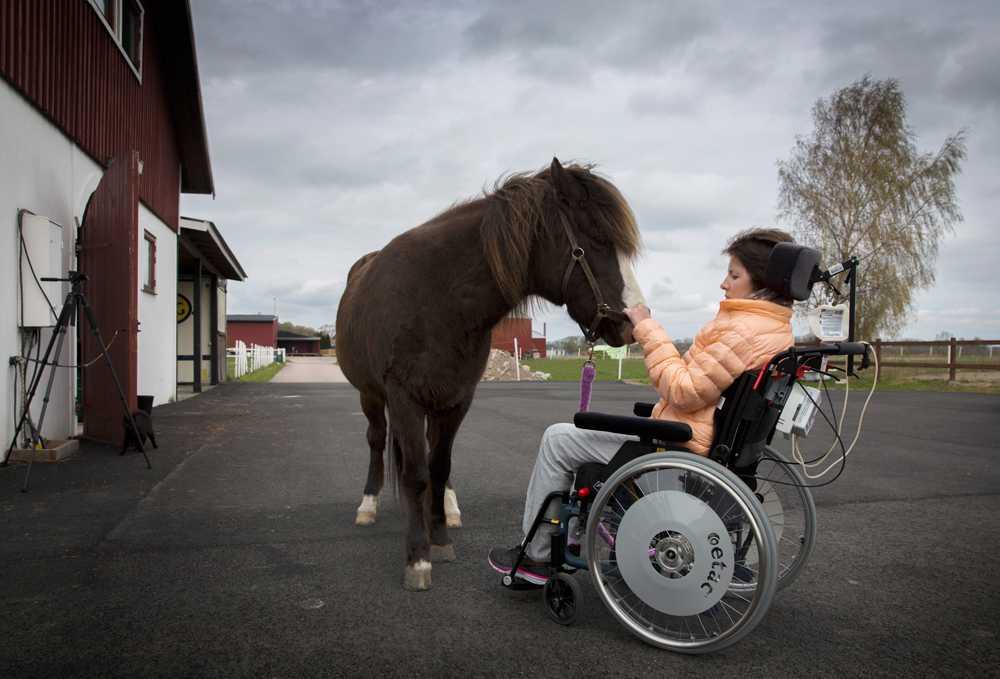 Nicole med sin islandshäst Ofelia. Hon rider  numera två gånger i veckan (skrittar) med två personer som stöd och en som leder hästen. Nicole har blivit starkare och stabilare.