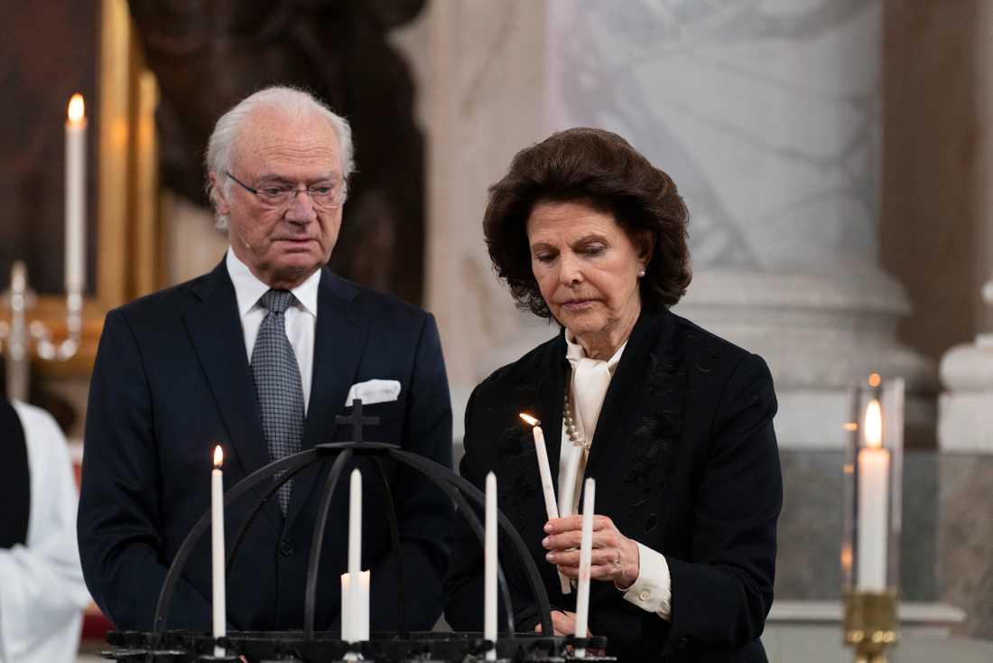 Kung Carl Gustaf och drottning Silvia tänder ljus under en gudstjänst i Drottningholms slottskyrka.