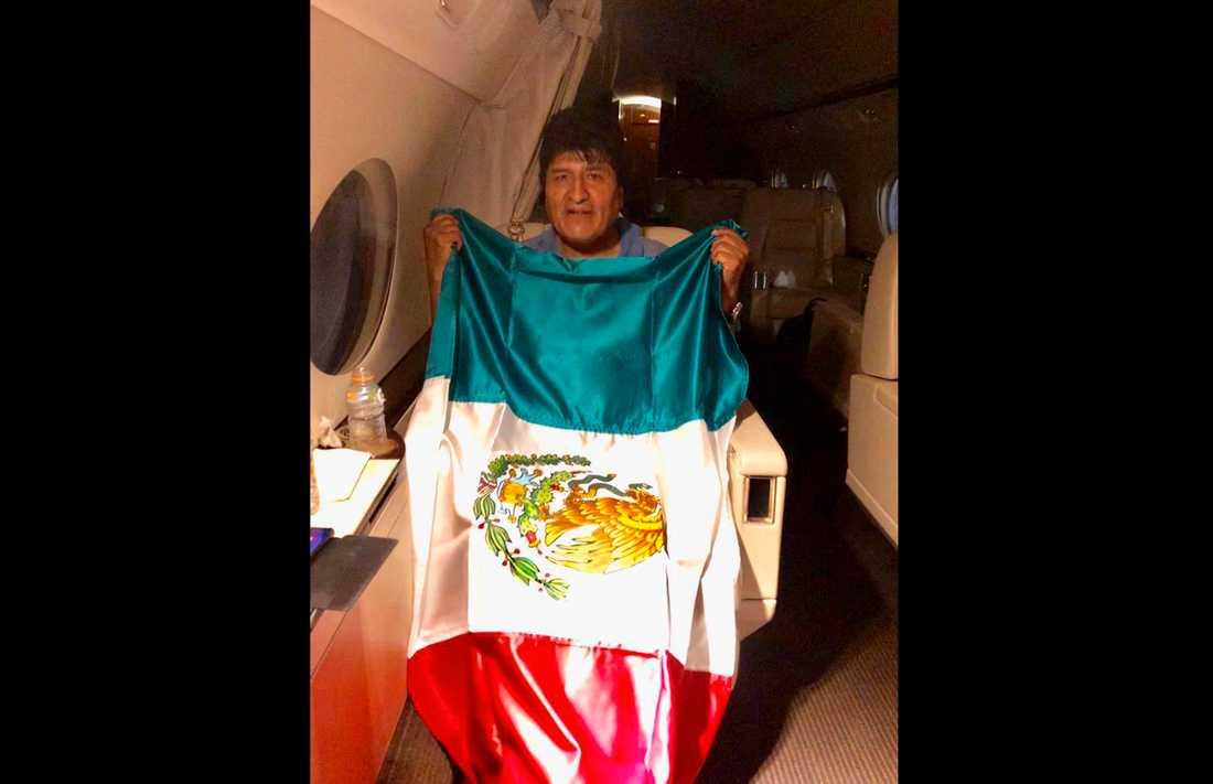 Evo Morales med en mexikansk flagga ombord på ett plan som ska ta honom till Mexiko. Bilden släpptes av den mexikanske utrikesministern Marcelo Ebrard.