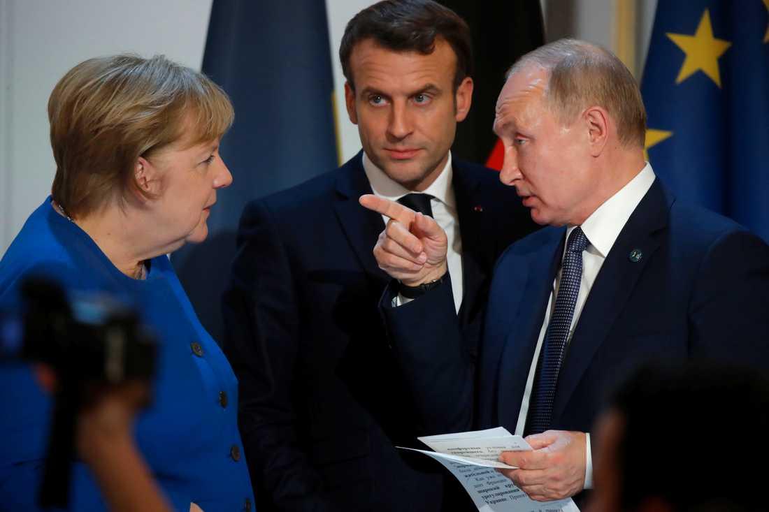 Tysklands förbundskansler Angela Merkel i samspråk med Vladimir Putin i Paris på måndagskvällen, med Frankrikes president Emmanuel Macron i bakgrunden.
