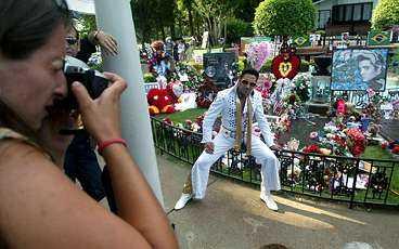 Elviskopiorna stod på kö för att fotografera sig vid Elvis grav som nästan täcktes av blommorna från fansen.