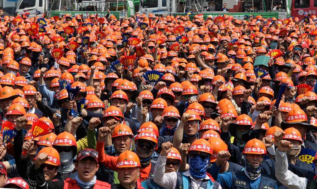 """Ett hav av arbetare samlas i Sydkoreas huvudstad Seoul. På hjälmarna står """"förenas, och kämpa""""."""