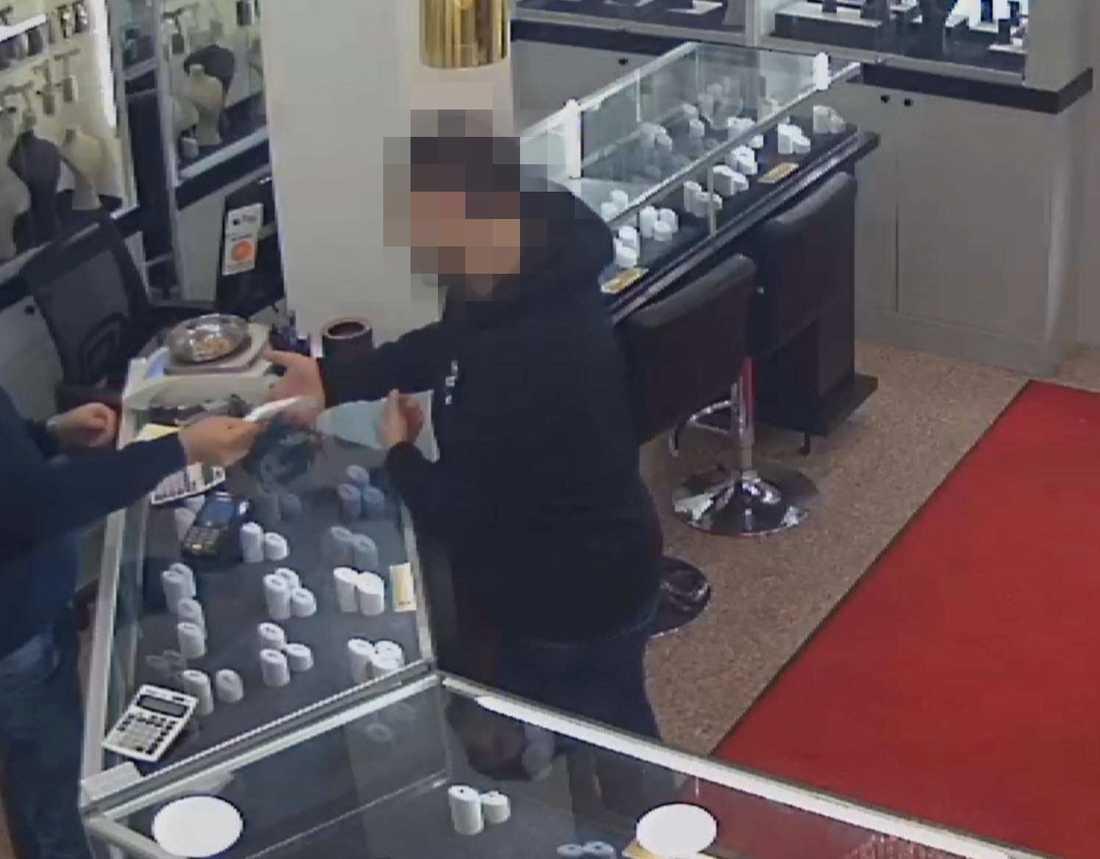 34-åringen betalar för smycken i en guldbutik.