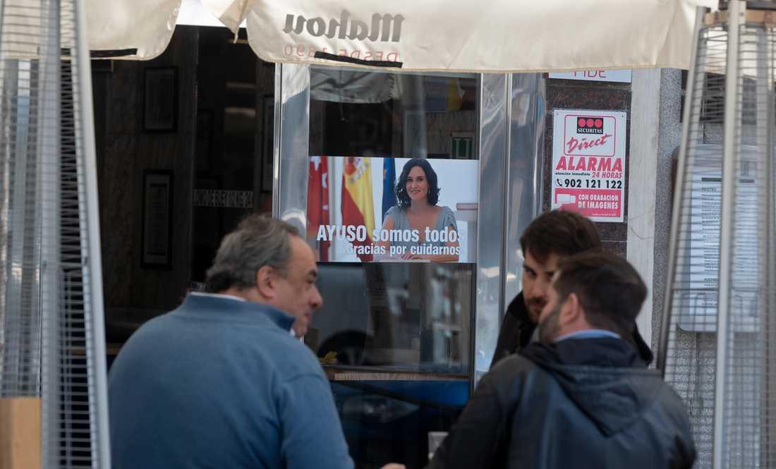"""Madrids konservative regionpresident Isabel Díaz Ayuso har gjort sig populär bland många genom att motsätta sig striktare coronarestriktioner. Här syns hon på en hyllningsaffisch på en bar med texten """"Tack för att du tar hand om oss""""."""