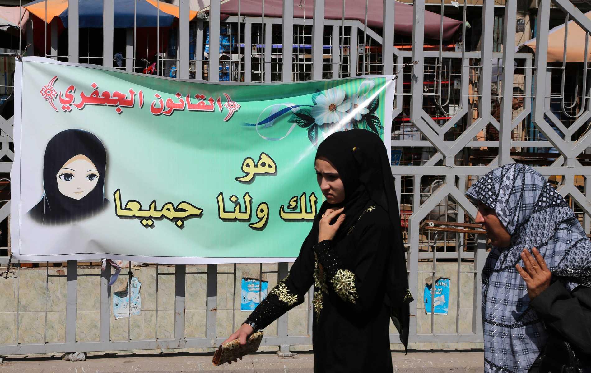 Flicka passerar poster för Jaafari-lagen i Irak.