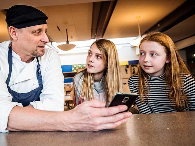 SMART SKOLMATSAL. Kocken David Clifford instruerar eleverna har Tilda Petrusson 12, och Moa Granhage, 13, i hur appen fungerar. Det är David Clifford som utvecklat den för att hjälpa barnen att se hur mycket de har slängt från tallrikarna.