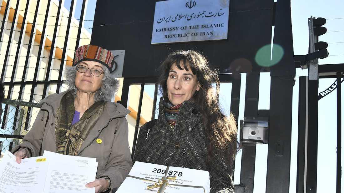 Andrea Bodekull och Maja Åberg, båda Amnesty, framför grinden till Irans Ambassad med namnunderskrifter. Arkvibild.