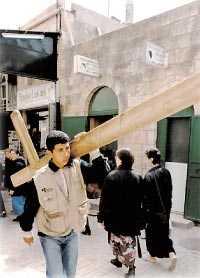 Jesus gata? En ung man går samma väg som Jesus sägs ha gått med sitt kors, på Via Dolorosa. Man kan hyra dessa kors.