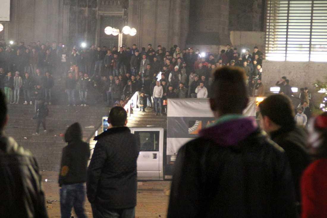 Folksamling framför tågstationen i Köln i Tyskland på nyårsafton där så många som nära 100 kvinnor polisanmält att de utsatts för sexuella övergrepp och rån.