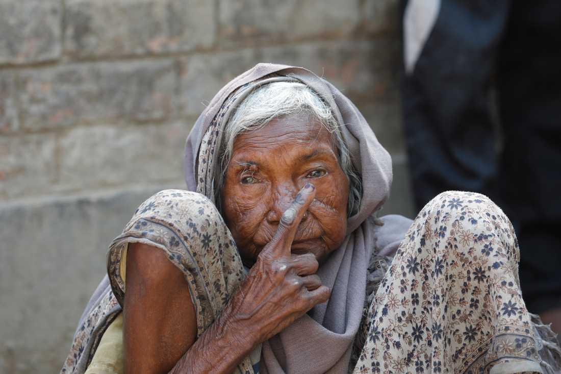 En äldre kvinna i Varanasi visar den bläckmärkning på fingret som visar att hon röstat i det indiska parlamentsvalet.