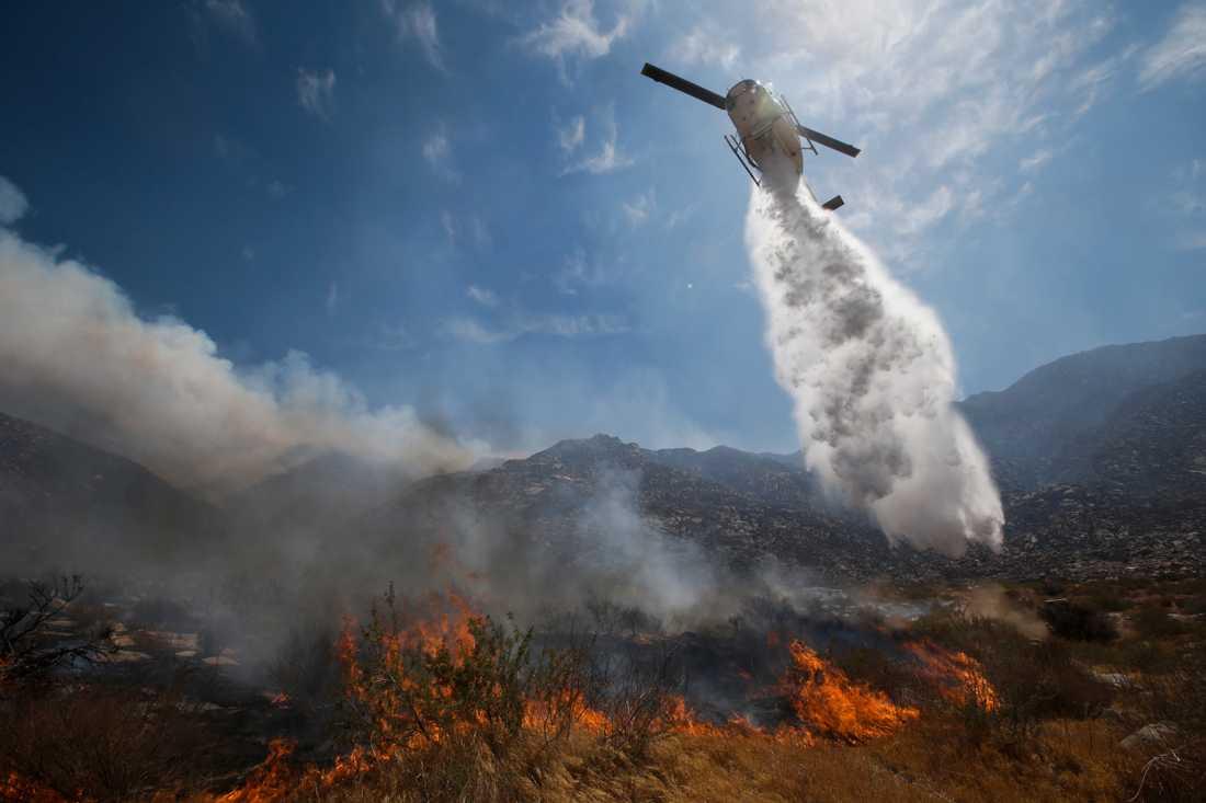 En skogsbrand i Kalifornien bekämpas med vatten från en helikopter. Branden, som sprider sig snabbt i södra delarna av delstaten, har tvingat omkring 1 500 människor att fly sina hem.