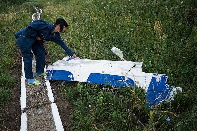 En kvinna som jobbar på det lokala vattenverket undersöker en del av det nedskjutna MH17-planet som inte tagits bort efter katastrofen.