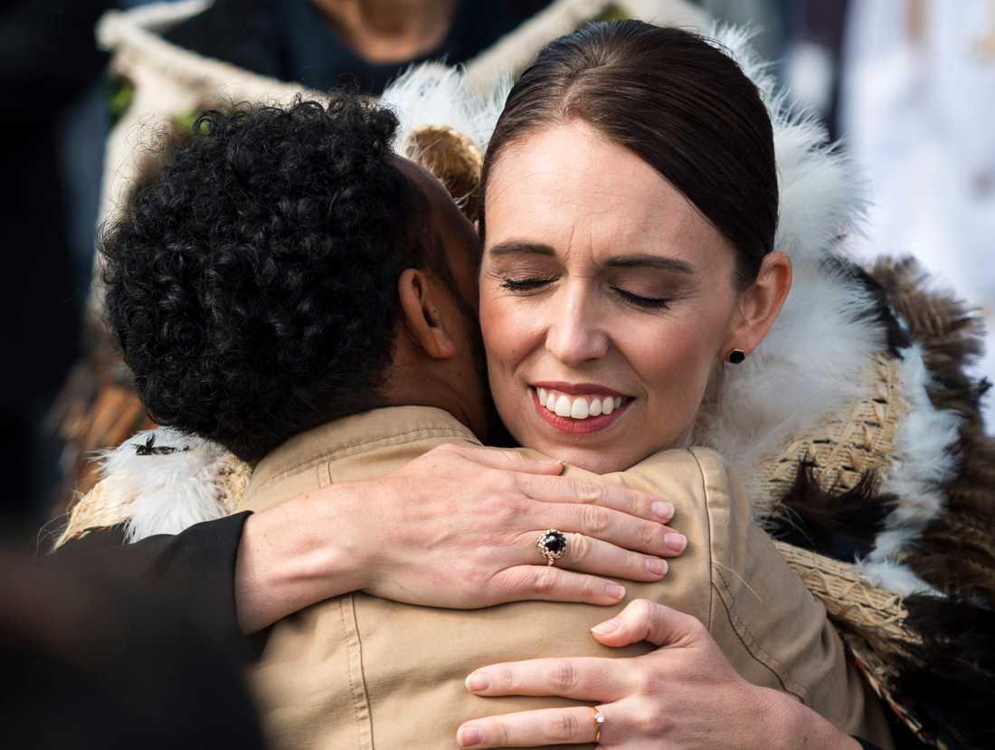 Jacinda Ardern omfamnar en besökare under ceremonin i Hagley Park i Christchurch.