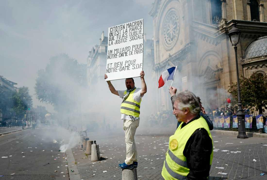 En förstamajdemonstrant protesterar mot att Macronregeringen satsar på återuppbyggnaden av Notre-Dame samtidigt som människor lever utan tak över huvudet i Frankrike.