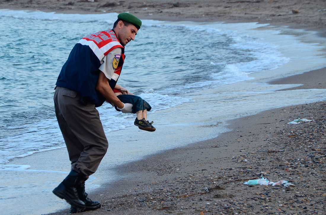 En turkisk gendarm bär bort lille Alans kropp från stranden i turkiska Bodrum för exakt ett år sedan.