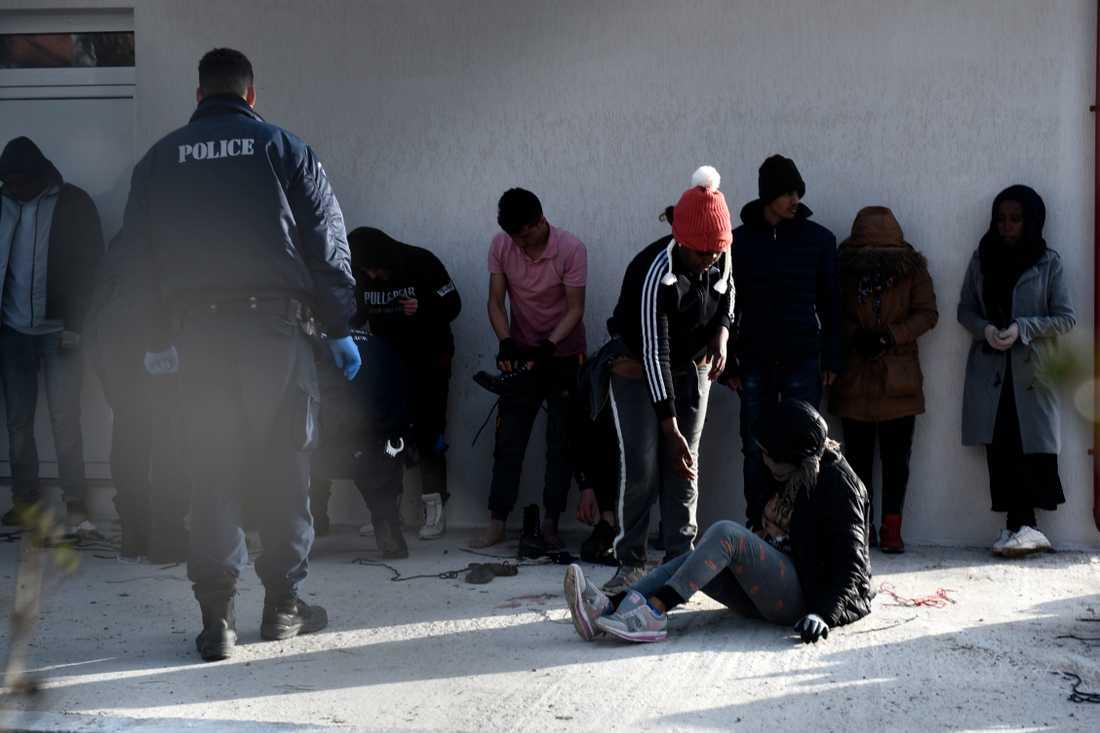 Grekisk polis kontrollerar tillfångatagna flyktingar vid en polisstation i byn Neo Cheimonio.