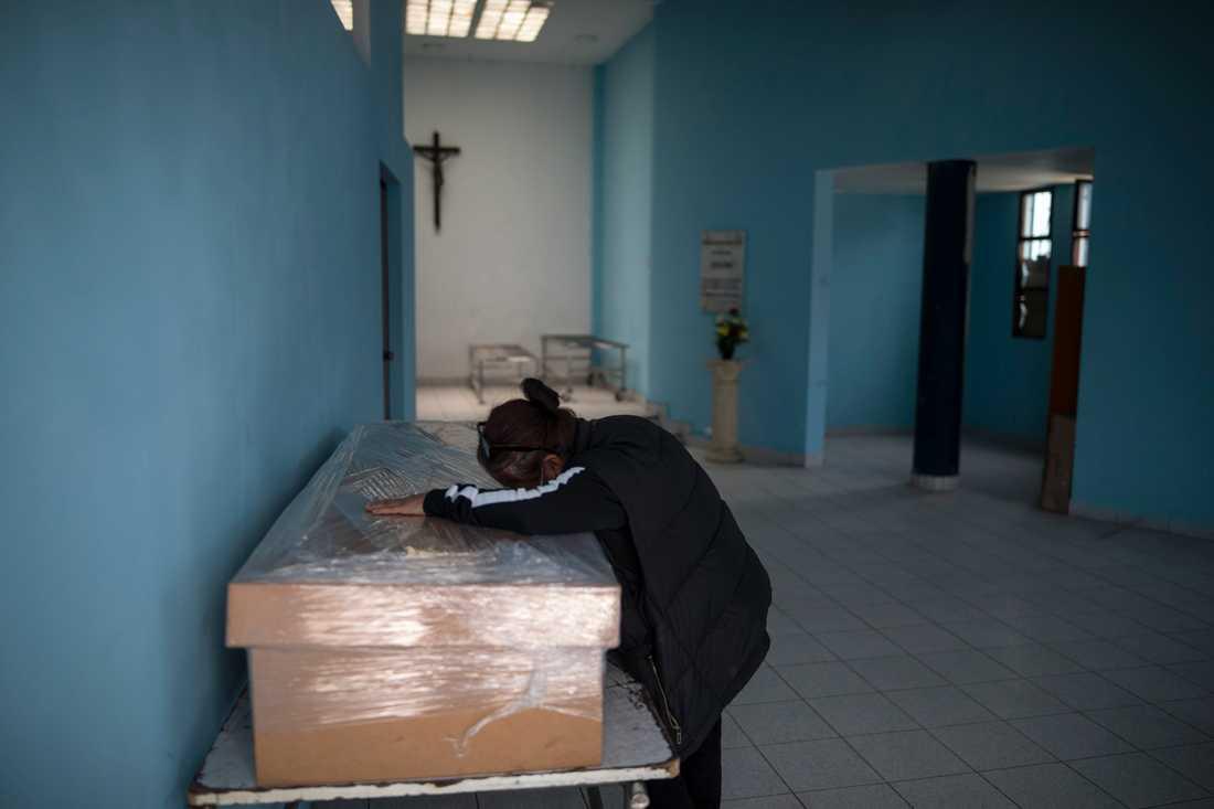 En änka sörjer sin make, som avlidit efter att ha insjuknat i covid-19, i Perus huvudstad Lima. Arkivbild.