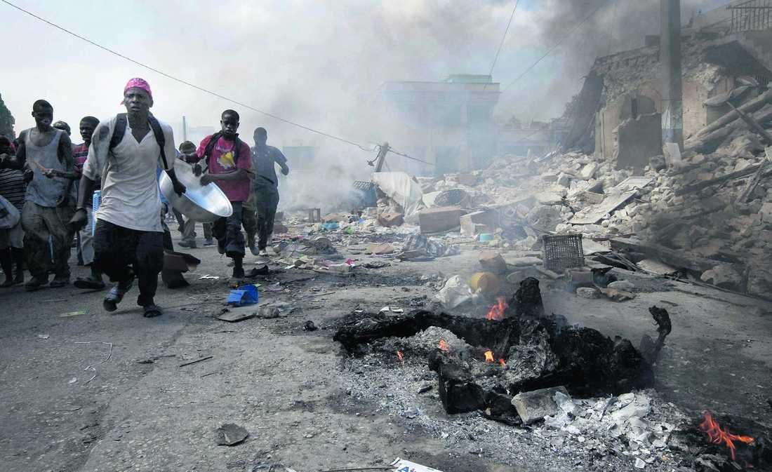 dödlig desperation Tusentals människor driver runt i huvudstaden Port-au-Prince på jakt efter mat, och kampen för överlevnad gör att de tar lagen i egna händer. Minst två plundrare har avrättats i gatans rättegångar och flera andra har misshandlats. |Haitis regering har utfärdat undantagstillstånd och uppger att 70 000 döda har begravts. Men kropparna tar inte slut. Invånarna har i desperation börjat bränna dem. Och nu är snart hoppet om att hitta fler överlevande i rasmassorna ute. Det har gått för lång tid.