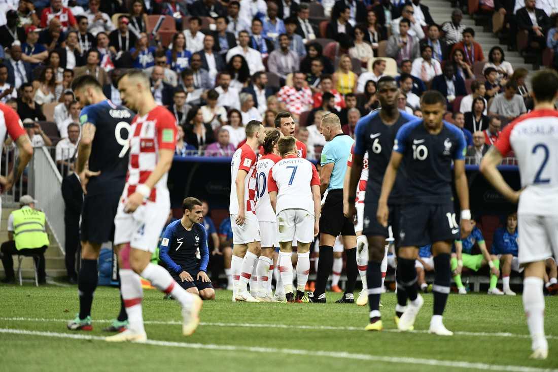 Kroatiska spelarna protesterar mot domslutet innan frisparken slås till Frankrikes 1–0-mål.