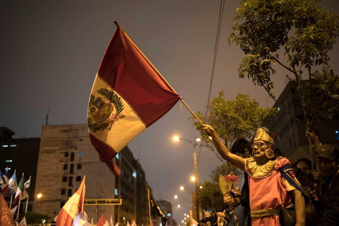 En anhängare till Perus president Martín Vizcarra med landets flagga efter att presidenten upplöst kongressen på måndagskvällen lokal tid.