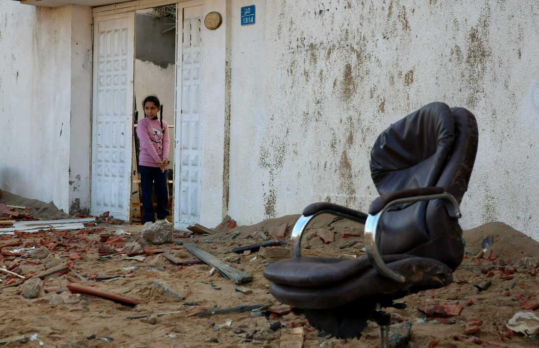 En palestinsk flicka tittar ut från familjens hus på tisdagen mot rester av Hamasledaren Ismail Haniyas högkvarter i Gazaremsan.