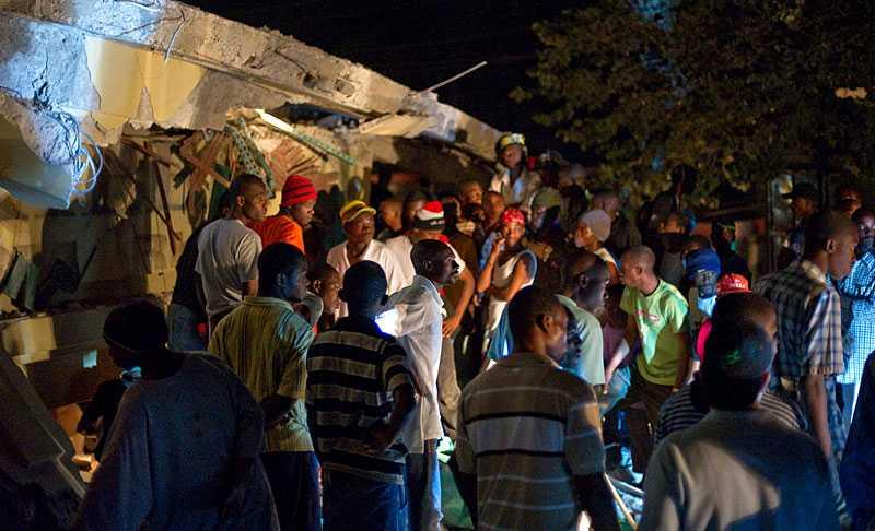 FÅNGADE I AFFÄREN Oroliga haitier samlades vid stormarknaden som rasade i skalvet för att söka sina anhöriga som befaras vara fångar under bråten efter skalvet.