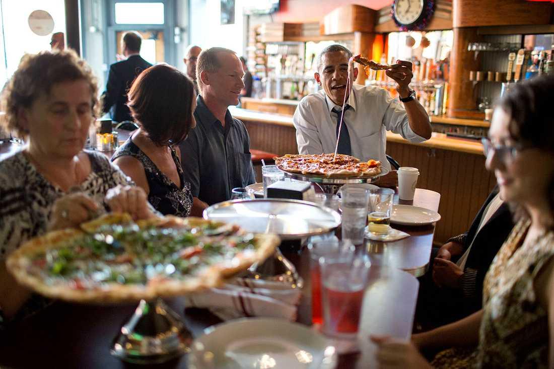 Obama på pizzafest tillsammans med en grupp människor som skrivit brev till presidenten.