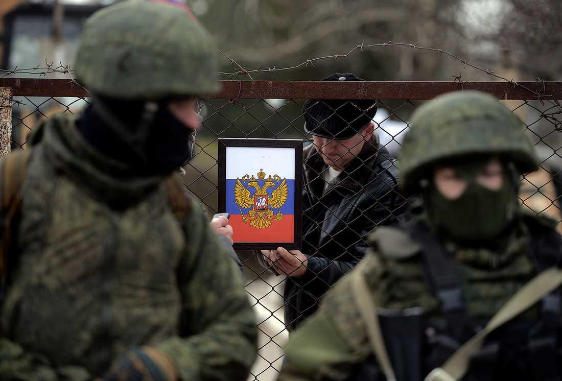 En man sätter upp den ryska örnen vid en checkpoint på Krim. I förgrunden ryska soldater.