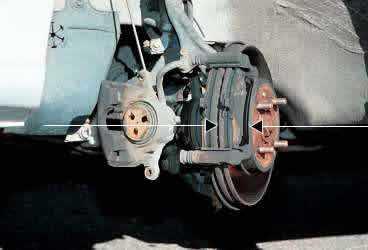 1. Bromsoket har skruvats bort och hängts upp i en ståltråd, ty den får aldrig hänga i bromsslangen. Konstruktionen fungerar som så att när du trycker ned bromspedalen klämmer bromsoket klossarna mot den roterande skivan (som pilarna visar), som då tvingas att stanna.