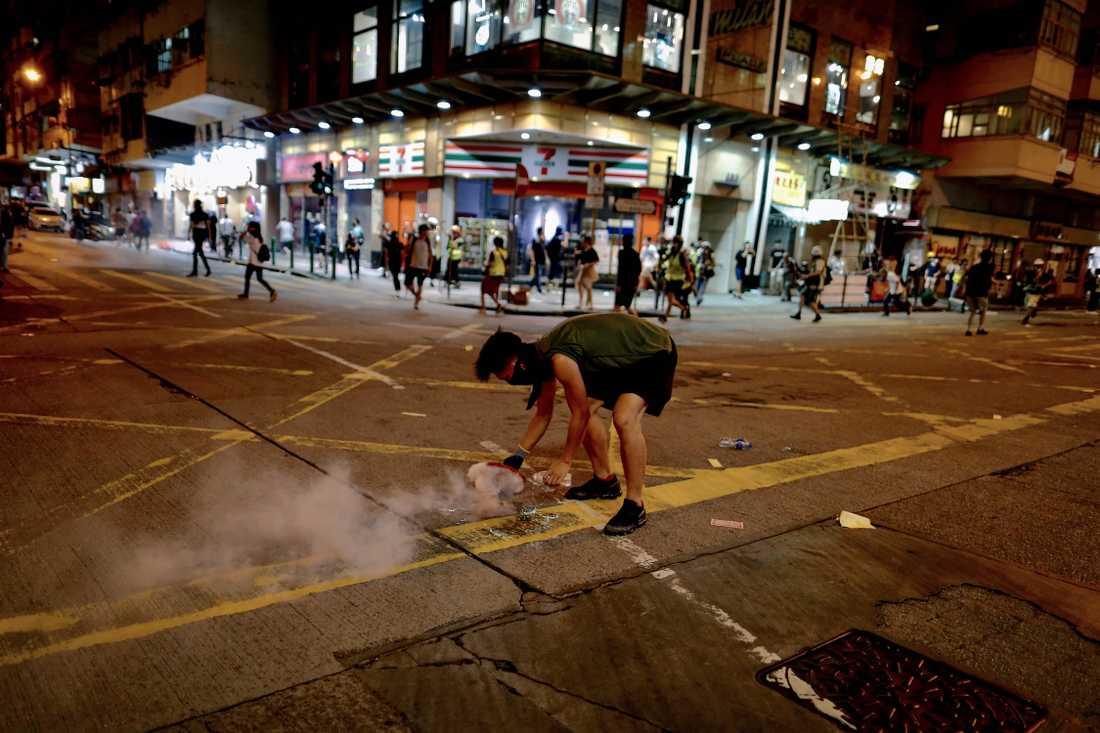 En demonstrant försöker täcka över en tårgasgranat under gatuprotesterna mot hårt kinesiskt styre i Hongkong..