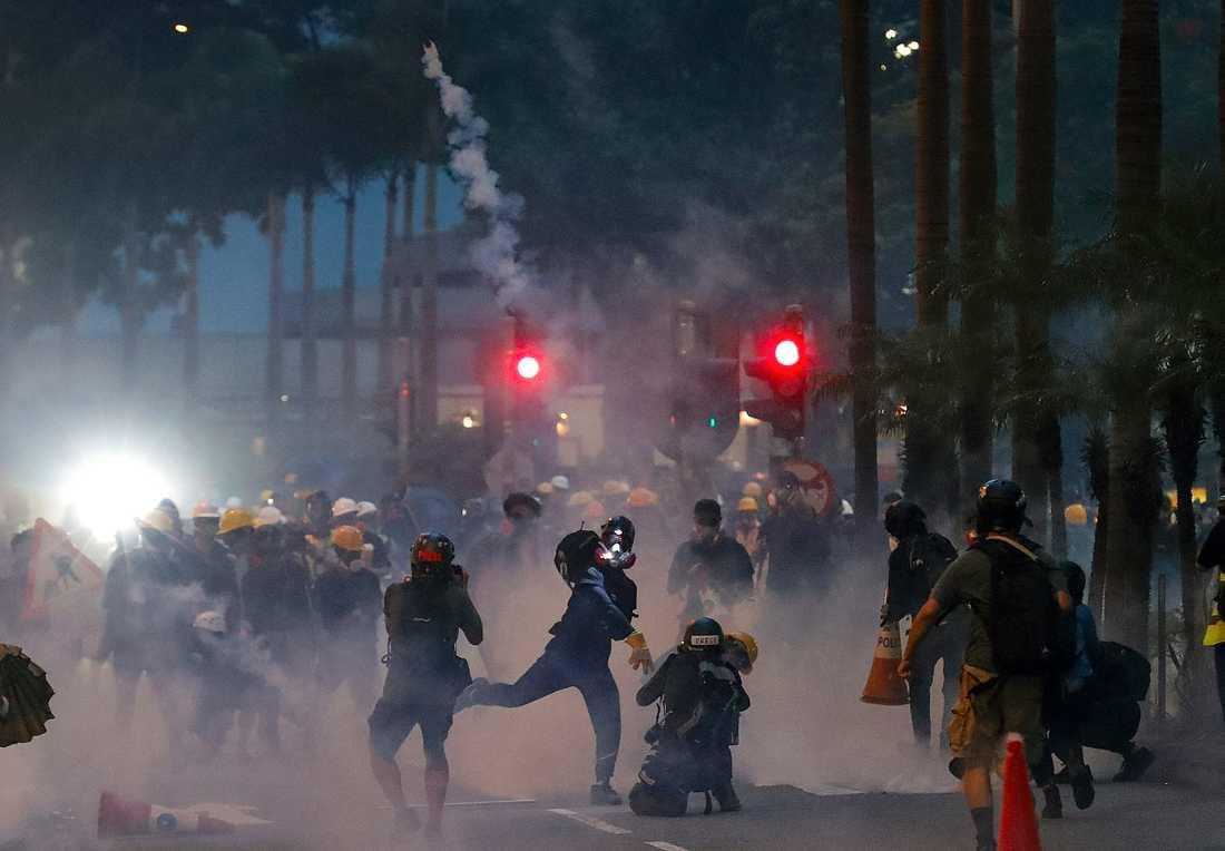 En demonstrant kastar tårgas avfyrad av polis under demonstrationerna på söndagen, då vilda protester återigen tog över gatorna i Hongkong.