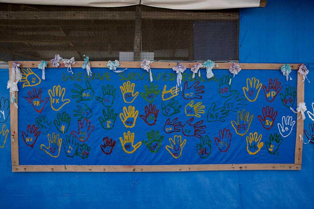 På en vägg till en administrationsbyggnad finns ett 40-tal handavtryck av dem som överlevt ebola.