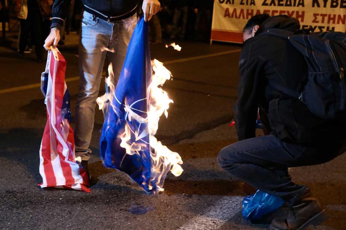 En demonstrant i Aten bränner USA:s och Natos flaggor under en minnesmarsch för att hedra offren i en studentprotest mot militärjuntan 1973.