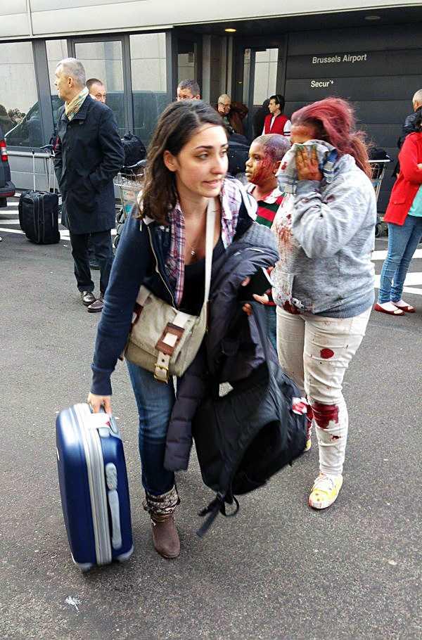 Skadade personer lämnar Bryssels flygplats.