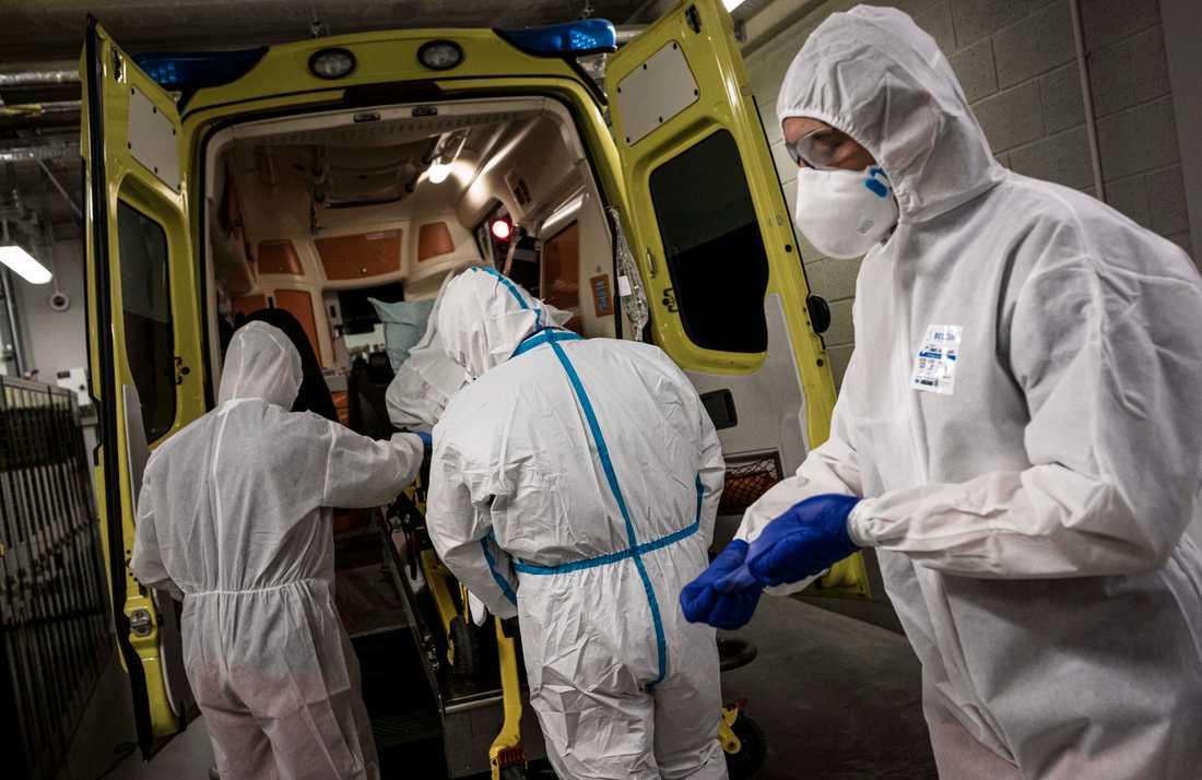 Sjukvårdspersonal i Liége förbereder för att ta ut en smittad patient ur en ambulans.