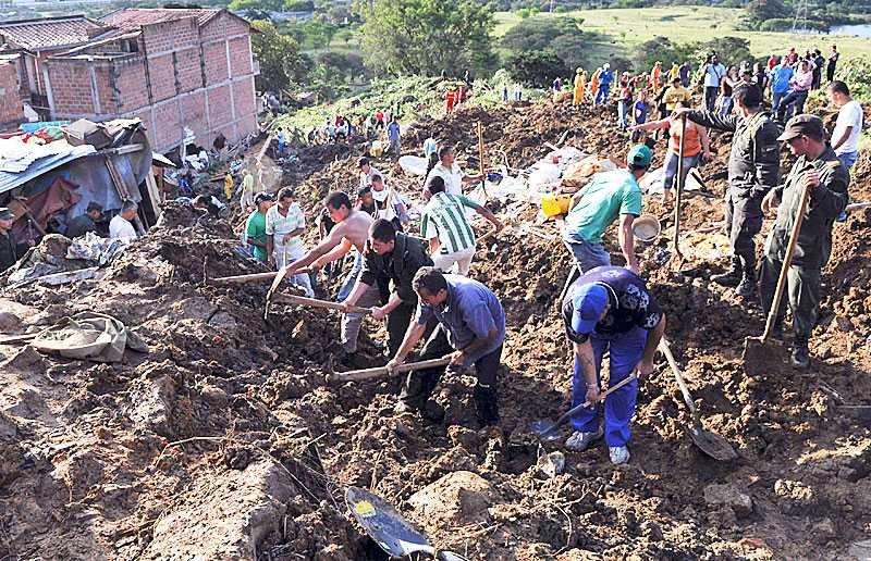 Polis och bybor gräver sig ner genom leran med hackor och spadar i jakt på överlevande i Bello.