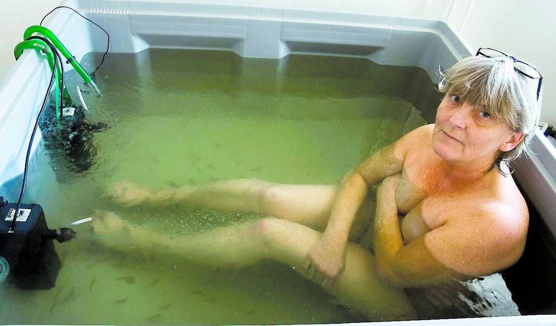Läkande Ensym Så snart Susanne Agregaard kliver ned i behandlingsbadet är de små Garra Rufafiskarna framme och börjar nafsa på hennes hud.