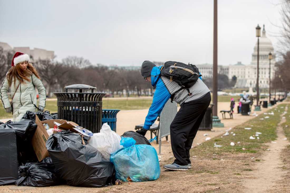 En frivilig tar hans om sopor vid grönområdet National Mall i USA:s huvudstad Washington DC. I bakgrunden syns kongressbyggnaden Capitolium, där en eventuell budgetuppgörelse om att öppna statsapparaten måste godkännas.