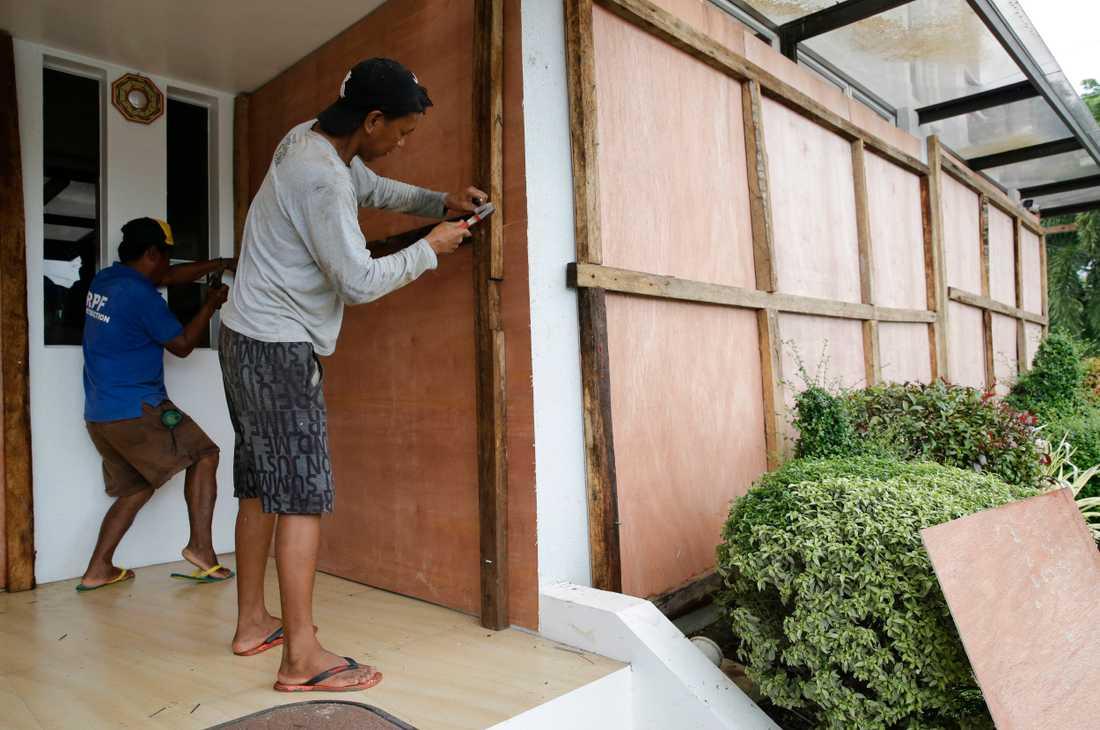 Arbetare täcker för fönstren till ett hotell med plywood-skivor inför tyfonen Mangkhuts framfart.