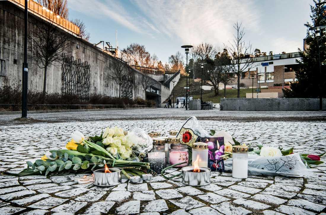 Blommor och ljus på torget i Vårby gård efter att en 63-årig man dödats av en handgranat i februari 2018.