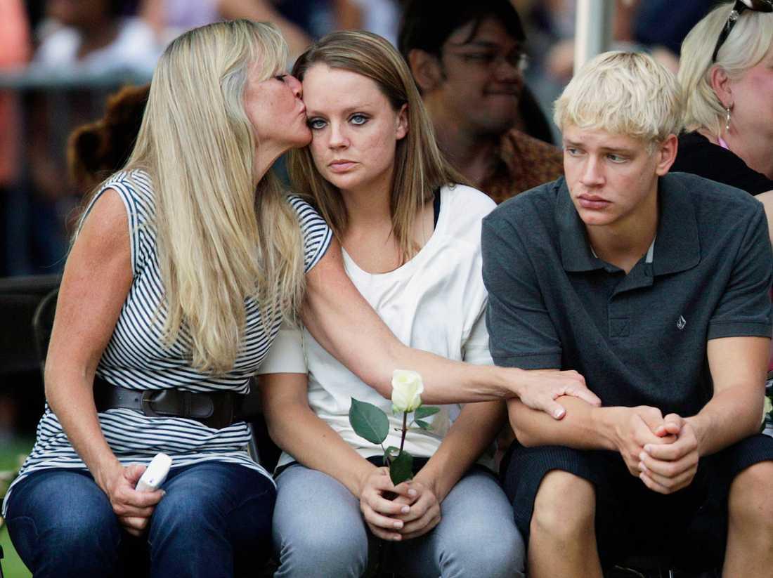 Släktingar till offren tröstar varandra under en minnesceremoni.