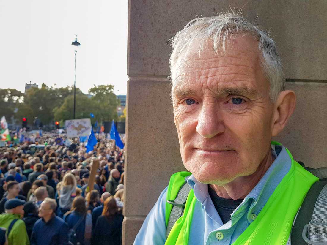 Alan Perry följer talen vid Parliament Square från en trappa.