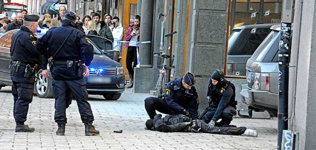 Polisen griper en av rånarna. I fönsterrutan syns fyra skotthål.