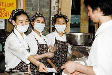 säljer snabblunch Tre kvinnor säljer lunchpaket utanför en restaurang i Kanton. I mataffärer och på krogar är munskydd närmast obligatoriskt, men bland vanligt folk på gatan är det inte många som bär mask. I Guangdong-provinsen har man lärt sig leva med sars-hotet hängande över sig.